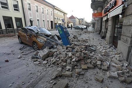 Trümmer eines durch ein Erdbeben eingestürzten Hauses bedecken ein Fahrzeug, das an einer Straße in Sisak steht. Foto: Marin Tironi/Pixsell/Xinhua/dpa