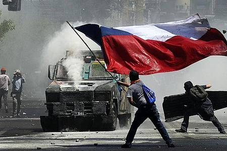 Flagge und Wasserwerfer: Momentaufnahme eines Protests in Chile gegen soziale Ungleichheit und die Regierung. Foto: Pablo Ovalle Isasmendi/Agencia Uno/dpa