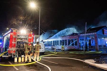Feuerwehrleute löschen einen brennenden Supermarkt in Berlin. Foto: Christophe Gateau/dpa