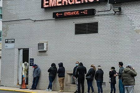 Menschen stehen vor einem Coronavirus-Testzentrum in New York Schlange. Foto: Marcus Santos/ZUMA Wire/dpa