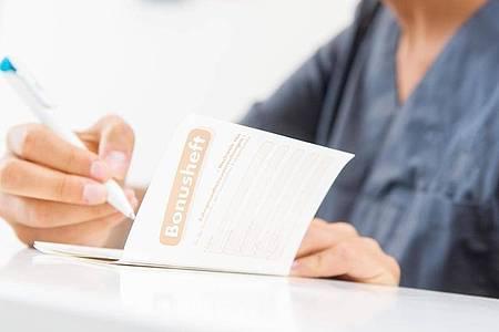 Lohnt sich: Ein lückenloses Bonusheft voller Zahnarztstempel sorgt für höhere Zuschüsse im Fall von Kronen, Brücken und Prothesen. Foto: Benjamin Nolte/dpa-tmn