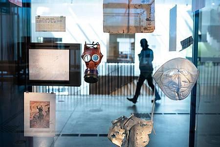 Eine Kindergasmaske und eine Frostschutzmaske hängen in einer Vitrine in der Ausstellung des neuen Dokumentationszentrums der Stiftung Flucht, Vertreibung, Versöhnung. Foto: Bernd von Jutrczenka/dpa