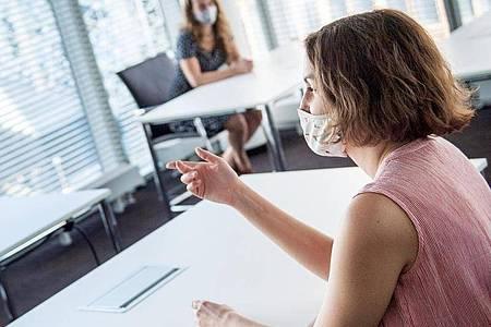 Mit Maske und Abstand gehen im Gespräch oft Infos verloren. Führungskräfte sollten ihre Mitarbeiter dafür sensibilisieren. Foto: Zacharie Scheurer/dpa-tmn