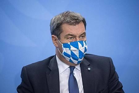 Markus Söder trägt während einer Pressekonferenz einen Mund-Nasen-Schutz. Foto: Stefanie Loos/AFP POOL/dpa