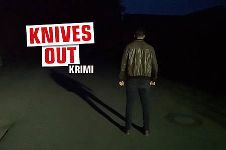 """Mann auf dunkler Straße mit Aufschrift """"Knives Out"""""""