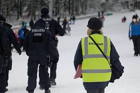 Polizisten und eine Mitarbeiterin des Ordnungsamtes stehen auf einer Piste im Skigebiet in Winterberg. Foto: Henning Kaiser/dpa