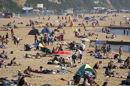 Zahlreiche Menschen genießen das warme Wetter am Strand von Bournemouth. Foto: Steve Parsons/PA Wire/dpa
