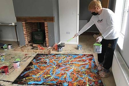 Auf den Spuren von Jackson Pollock:Ed Sheeran bei der Arbeit an einem seiner Gemälde. Foto: Made In Suffolk Legacy Auction/PA Media/dpa