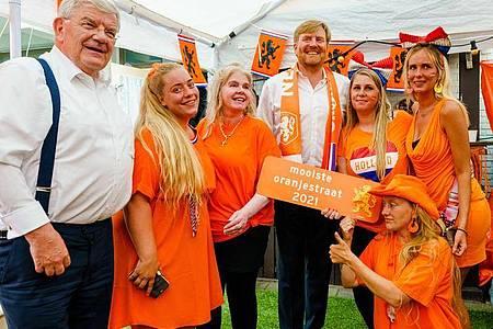 Dicht an dicht: König Willem-Alexander von den Niederlanden (M.) besucht Fußballfans an der schönsten Oranjestraat des Landes. Foto: Marco De Swart/ANP/dpa
