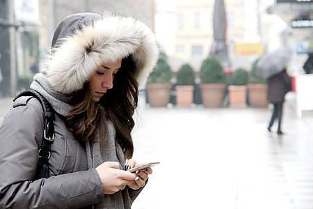 Frau guckt traurig auf ihr Smartphone