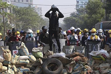 Ein Demonstrant steht während eines Protestes gegen den Militärputsch in Yangon auf einer Barrikade. Foto: Str/AP/dpa