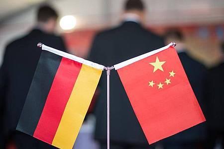 Eine chinesische und eine deutsche Flagge stehen am bei einem Empfang im chinesischen Hefei (China). Foto: picture alliance/Ole Spata/dpa