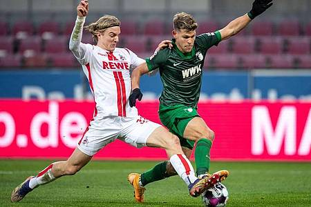 Kölns Sebastian Bornauw (l) im Zweikampf mit Augsburgs Florian Niederlechner. Foto: Marius Becker/dpa