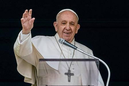Papst Franziskus winkt aus dem Fenster seines Arbeitszimmers mit Blick auf den Petersplatz einer Menge von Gläubigen und Pilgern zu. Foto: Domenico Stinellis/AP/dpa