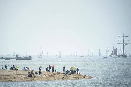 Menschen beobachten Segelschiffe während der traditionellen Windjammerparade zum Abschluss der Kieler Woche in der Kieler Förde. Foto: Gregor Fischer/dpa