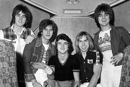 Stuart Wood (l-r), Alan Longmuir, Leslie Mckeown, Derek Longmuir und Eric Faulkner warten in einem Jumbo-Jet auf dem Londoner Flughafen Heathrow auf den Abflug zu einer Tournee durch Australien (1975). Foto: Pa/PA Wire/dpa