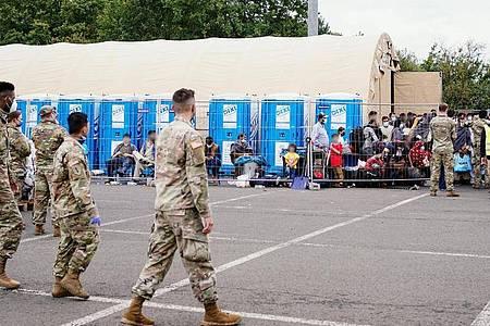 Aus Afghanistan evakuierte Menschen stehen auf der Ramstein Air Base vor einem Zelt. Davor gehen US-Soldaten. Foto: Uwe Anspach/dpa