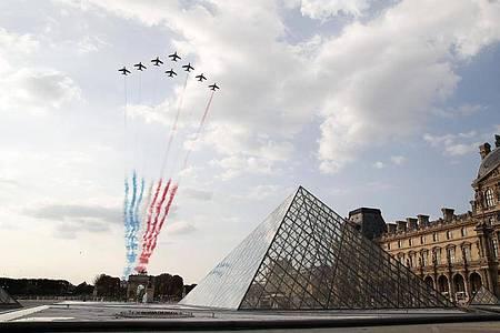 Flugzeuge der Kunstflugstaffel «Patrouille de France» zeichnen die französische Nationalflagge über demMuseum Louvre an den Himmel. Foto: Francois Mori/AP/dpa