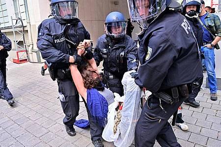 Eine Protestteilnehmerin wird von Polizisten weggetragen. Foto: Peter Kneffel/dpa