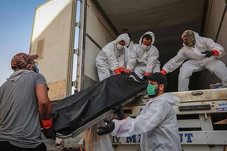 Arbeiter in Schutzkleidung beladen in Bagdad einen Kühlwagen mit Leichen von Menschen, die am Coronavirus gestorben sind. Foto: Ameer Al Mohammedaw/dpa