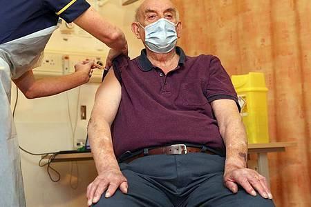 Der 82-jährige Brian Pinker erhält im Churchill Hospital als erster Brite den Corona-Impfstoff der Universität Oxford und des Pharmakonzerns Astrazeneca von der Krankenschwester Sam Foster. Großbritannien hatte dem Präparat in der vergangenen Woche eine Notfallzulassung erteilt. Foto: Steve Parsons/PA Wire/dpa