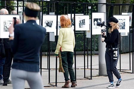 Spaziergänger schauen sich die Outdoor-Fotoausstellung im Rahmen der Ruhrfestspiele am Festspielhaus an. Foto: Roland Weihrauch/dpa