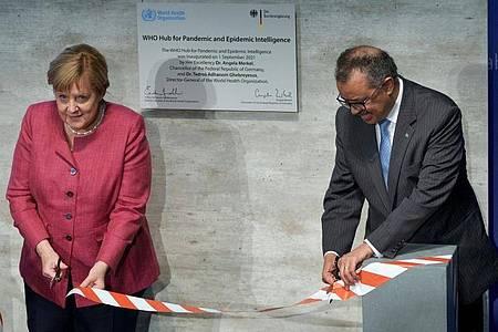 """Tedros Adhanom Ghebreyesus, Generaldirektor der Weltgesundheitsorganisation (WHO), und Bundeskanzlerin Angela Merkel (CDU) bei der Einweihungszeremonie des """"WHO Hub For Pandemic And Epidemic Intelligence"""". Foto: Michael Sohn/POOL AP/dpa"""