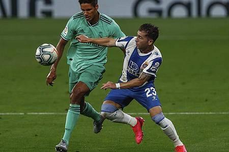 Raphael Varane (l) von Real Madrid kämpft mit Gegenspieler Adri Embarba um den Ball. Foto: Joan Monfort/AP/dpa