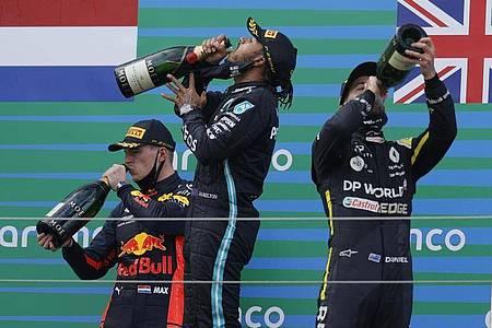 Auf dem Podest genehmigen sich der Zweitplatzierte Max Verstappen (l-r), Sieger Lewis Hamilton und Daniel Ricciardo zunächst einen großen Schluck. Foto: Ronald Wittek/Pool EPA/AP/dpa