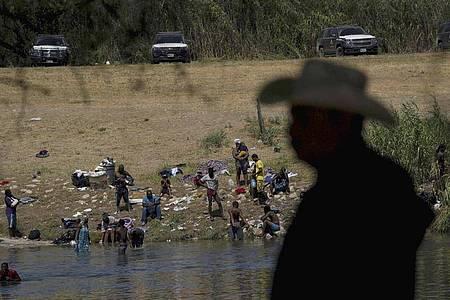 Migranten, viele von ihnen aus Haiti, überqueren den Rio Grande in Del Rio, um nach Ciudad Acuna zurückzukehren. Foto: Fernando Llano/AP/dpa