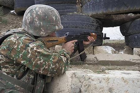 Ein armenischer Soldat zielt in Richtung der aserbaidschanischen Stellungen. Foto: -/AP/dpa