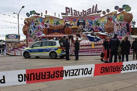 Polizisten und ein Polizeiwagen stehen vor dem Fahrgeschäft «Playball» beim «Potsdamer Oktoberfest». Foto: Julian Stähle/dpa-Zentralbild/dpa