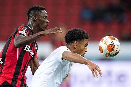 Leverkusens Odilon Kossounou (l) und Budapests Ryan Mmaee kämpfen um den Ballbesitz. Foto: Marius Becker/dpa