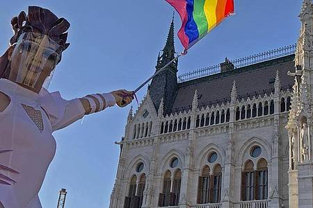 Eine Drag Queen schwenkt eine Regenbogenfahne auf einer LGBT-Rechte-Demonstration vor dem ungarischen Parlament. Foto: Bela Szandelszky/AP/dpa
