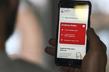 Auf einem Handy zeigt die «Corona Warn-App» ein erhöhtes Risiko an, wenn ein längerer Kontakt mit einer infizierten Person registriert wurde. Foto: Kira Hofmann/dpa-Zentralbild/dpa