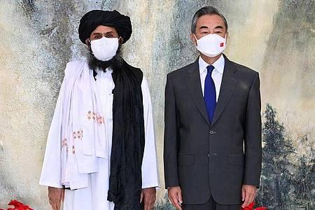 Chinas Außenminister Wang Yi (r) neben einem Führer der Taliban. Foto: Li Ran/XinHua/dpa