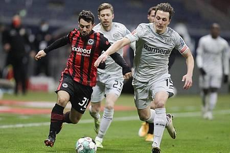 Frankfurts Amin Younes (l) im Zweikampf mit Leverkusens Julian Baumgartlinger. Foto: Michael Probst/AP-Pool/dpa