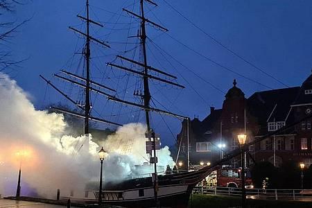 Rauch und Dampf steigt aus dem Museumsschiff «Friederike von Papenburg». Es hatte am Samstagmorgen Feuer gefangen. Foto: NWM/dpa