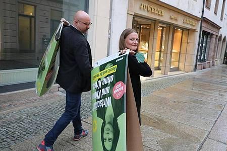 Wolfgang Wetzel, (l) Spitzenkandidat der Grünen und Christin Furtenbacher, Landesvorstandssprecherin der Grünen in Sachsen, laufen mit Wahlplakaten durch die Innenstadt von Zwickau. Foto: Bodo Schackow/dpa-Zentralbild/dpa