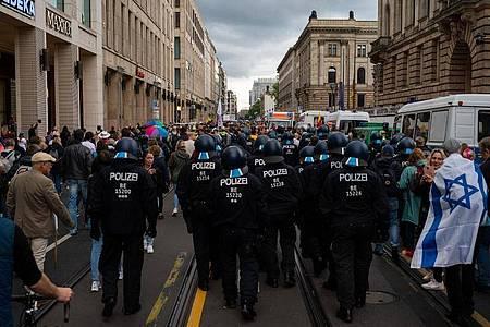 Polizisten folgen nach dem Ende einer Kundgebung gegen die Corona-Politik der Regierung den Teilnehmern. Foto: Paul Zinken/dpa