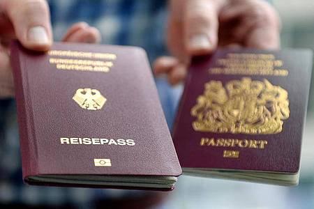 Ein britischer und ein deutscher Reisepass. Bis auf wenige Ausnahmen reicht ab dem 01.10.2021 an ein Personalausweis nicht mehr aus, um in Großbritannien zu kommen. Foto: Britta Pedersen/zb/dpa
