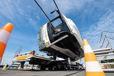 Bei dem Versuchsaufbau auf dem Crashtestgelände kippt ein kleiner mit Insassen besetzter Reisebus per Hydraulik um 90 Grad auf die Seite. Foto: Guido Kirchner/dpa
