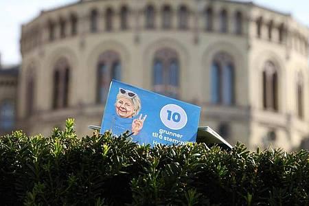 Ein Flyer der norwegischen Regiergungschefin Erna Solberg steckt vor dem Parlament in Oslo in einer Hecke. Bewahrheiten sich die Umfragen, dann ist die Regierungszeit der konservativen Ministerpräsidentin nach acht Jahren zu Ende. Foto: Steffen Trumpf/dpa