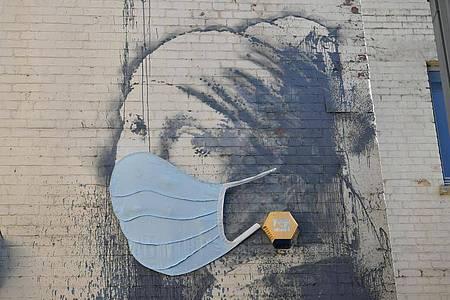 """Das Wandgemälde """"Das Mädchen mit dem Perlenohrring"""" in Bristol, das von Banksy stammen soll, hat als Reaktion auf die Coronavirus-Pandemie eine Gesichtsmaske bekommen. Foto: Ben Birchall/PA Wire/dpa"""