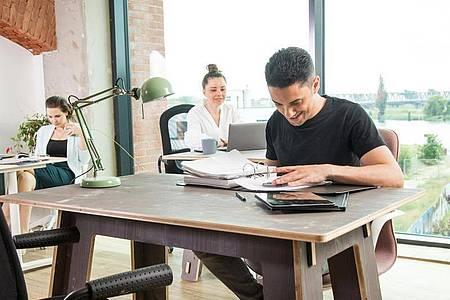 Jeder Mitarbeiter sucht sich morgens einen freien Tisch. Foto: Christin Klose/dpa-tmn