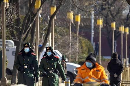 Chinesische paramilitärische Polizisten mit Mund-Nasen-Schutz patrouillieren entlang einer Straße in Peking. Foto: Mark Schiefelbein/AP/dpa