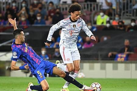 Barcelonas Mittelfeldspieler Sergio Busquets (l) rettet gegen Leroy Sané. Foto: Sven Hoppe/dpa