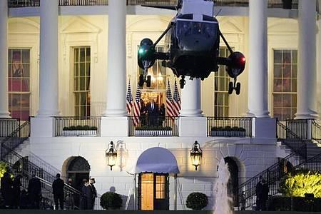 US-Präsident Trump beobachtet vom Balkon des Weißen Hauses aus, wie die Marine One startet. Foto: J. Scott Applewhite/AP/dpa
