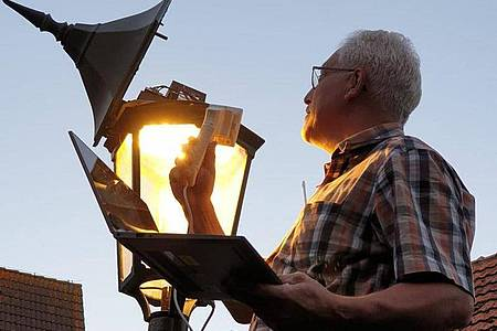 Spiekeroogs Bürgermeister Matthias Piszczan programmiert die Helligkeit einer Straßenlaterne um. Foto: Andreas Hänel/dpa