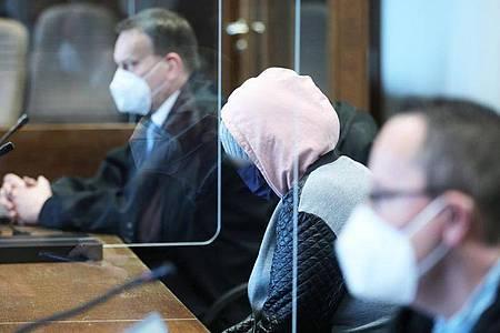 Die angeklagte Mutter (m.) zwischen Anwälten im Gerichtssaal in Köln. Foto: Oliver Berg/dpa